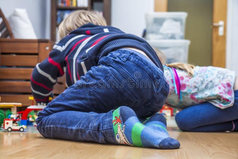 Deux petits enfants jouant avec des briques sur le plancher photos stock