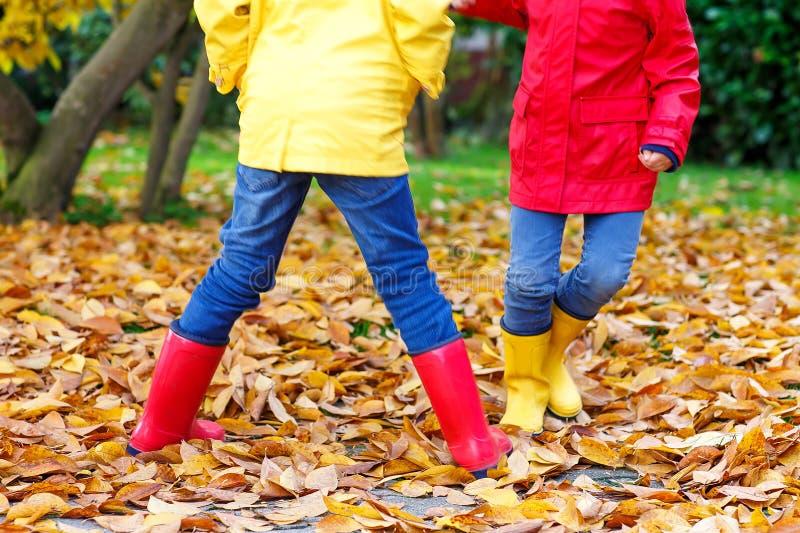 Deux petits enfants jouant dans des bottes en caoutchouc rouges et jaunes en automne se garent dans les manteaux et des vêtements photo stock
