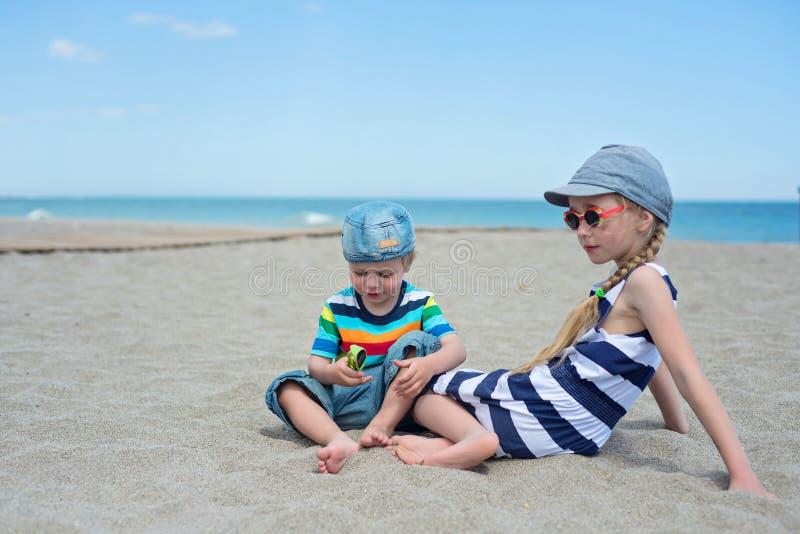 Deux petits enfants s'asseyant sur la plage photographie stock