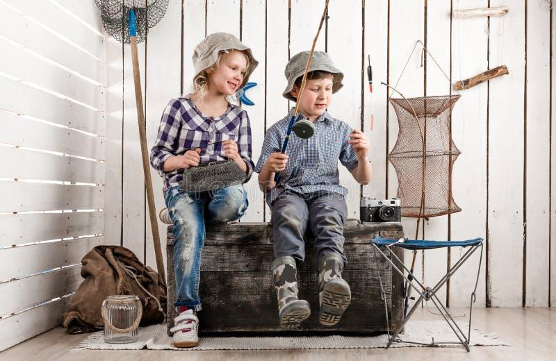 Deux petits enfants sur le coffre préparent l'amorce sur la tige photographie stock libre de droits