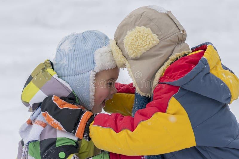 Deux petits frères heureux jouant pendant l'hiver dehors Deux petits frères heureux en hiver dehors deux petits garçons en hiver photos stock