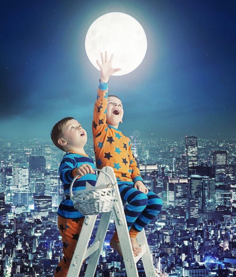 Deux petits frères sur l'échelle au ciel photos stock