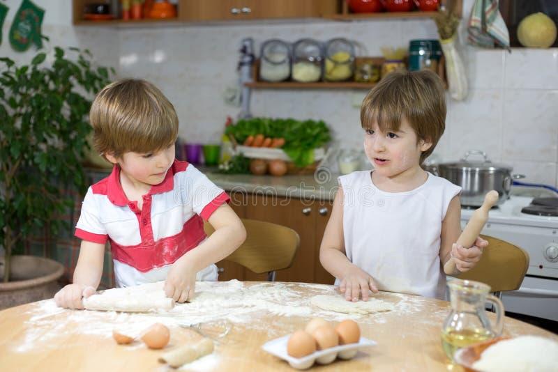 Deux petits garçons jouant avec la pâte à la table de cuisine image stock