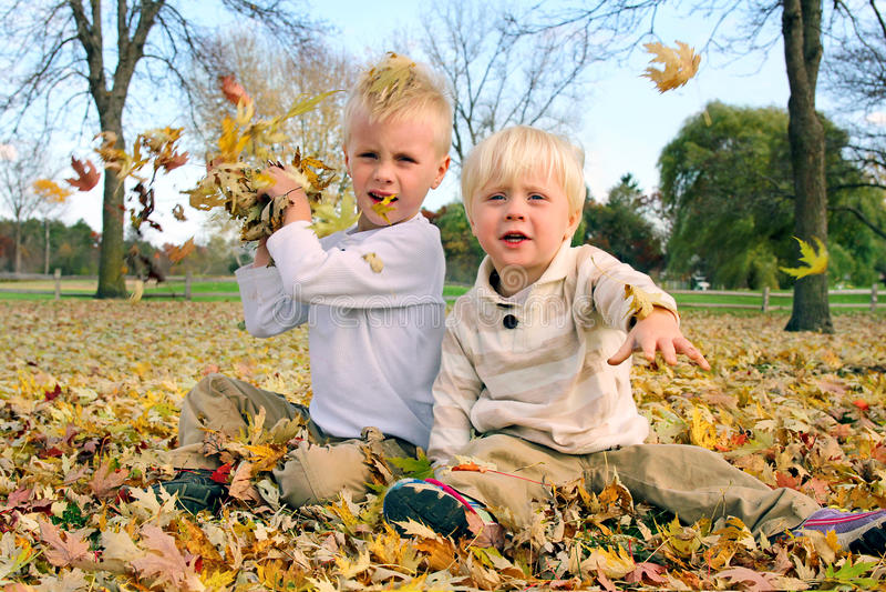 Deux petits garçons jouant les feuilles de lancement d'automne d'extérieur photographie stock libre de droits
