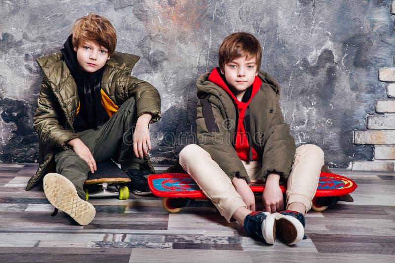 Deux petits garçons jumeaux dans des vêtements sport se reposant sur la planche à roulettes dans le studio Ado et concept de mode image stock
