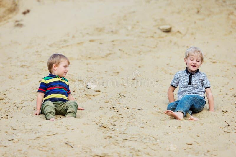 Deux petits garçons sur le sable échouent au lac photographie stock