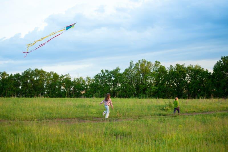 Deux petits gosses pilotent un cerf-volant photos libres de droits