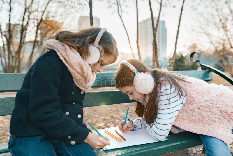 Deux petits jolis artistes dessinant avec les crayons colorés, filles s'asseyant sur un banc en parc ensoleillé d'automne, heure  image libre de droits