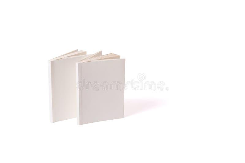 Deux petits livres brochés blancs se tiennent sur une surface blanche du côté gauche Peut être employé pour des maquettes De reto image stock
