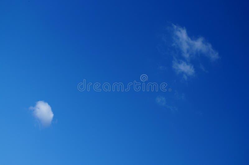 Deux petits nuages perdus dans le ciel bleu photo libre de droits