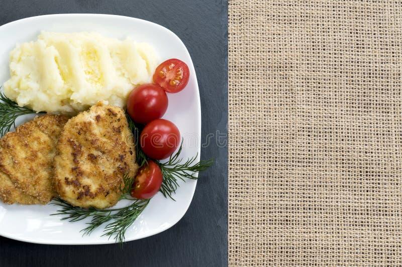 Deux petits pâtés frits juteux de viande d'un plat blanc avec des tomates-cerises images libres de droits