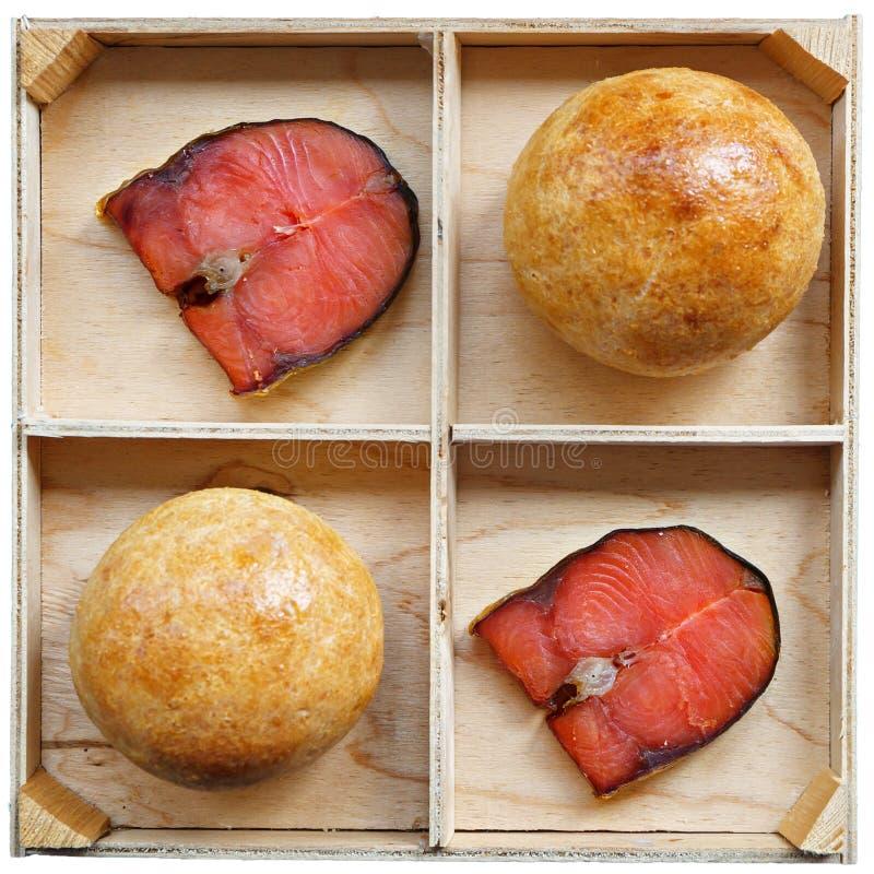 Deux petits pains de sandwich et 2 morceaux de mensonge rouge de poissons sur un support en bois Ingr?dients de nourriture sains  photo libre de droits