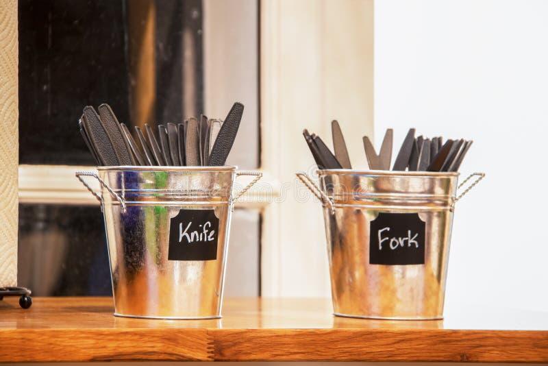 Deux petits seaux de bidon sur le compteur au restaurant tenant les couverts en plastique - couteaux et fourchettes - foyer sélec photos libres de droits