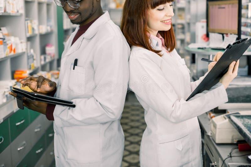 Deux pharmaciens multiraciaux travaillant dans la position de pharmacie de nouveau au dos Mâle et pharmaciens féminins vérifiant  photos stock