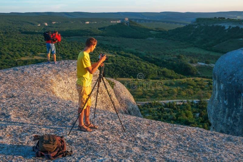 Deux photographes prend des photos de nature sur la roche photographie stock libre de droits