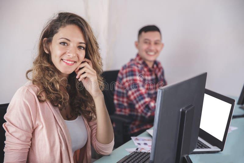 Deux photographes souriant tout en éditant des photos dans leur ordinateur images stock