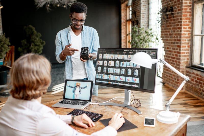 Deux photographes travaillant sur les ordinateurs dans le studio image libre de droits
