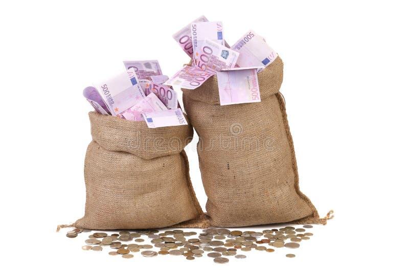 Deux pleins sacs avec l'argent et les pièces de monnaie. photographie stock libre de droits