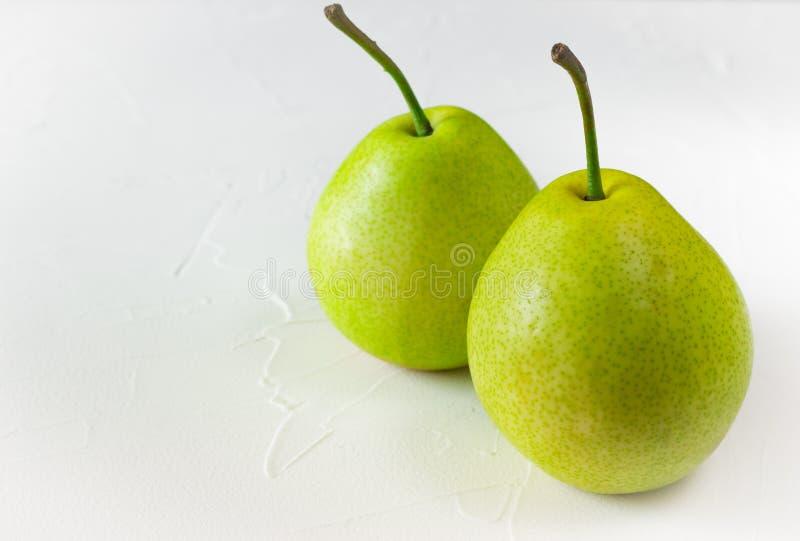 Deux poires mûres vertes sur le fond concret blanc photo stock