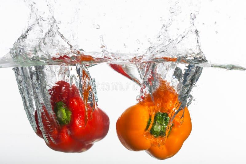 Deux poivrons clairs est projetés dans l'eau propre. images stock