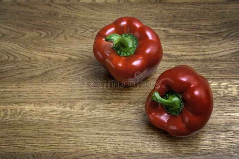Deux poivrons rouges sur une table en bois brune photographie stock libre de droits