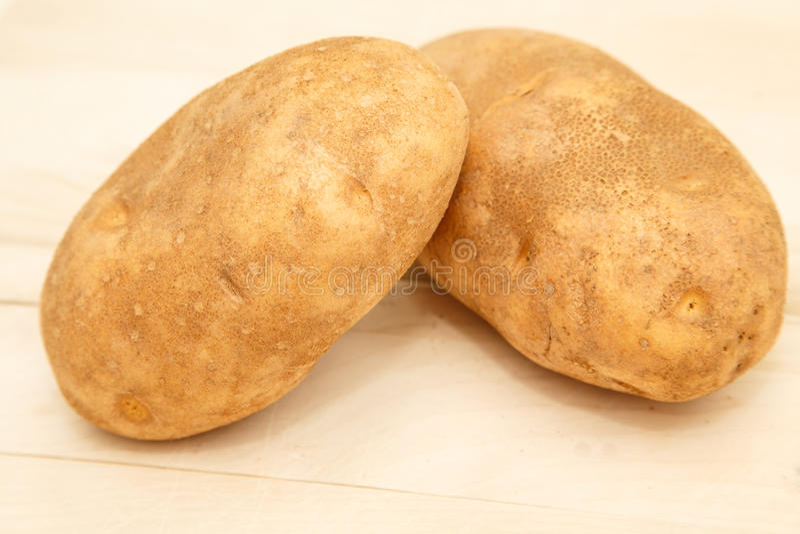 Deux pommes de terre entières sur la planche à découper pour la cuisson photos stock