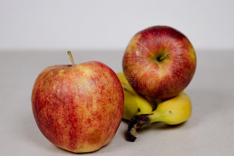 Deux pommes et deux bananes d'isolement sur un fond de Gray White Grey Marble Slate photos stock