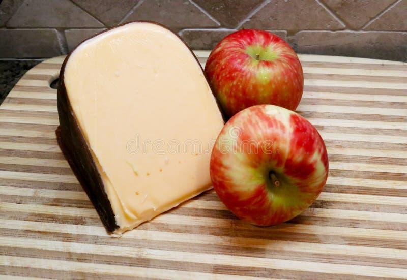 Deux pommes et gouda fumé sur le bloc du ` s de boucher avec le fond de tuile photo libre de droits