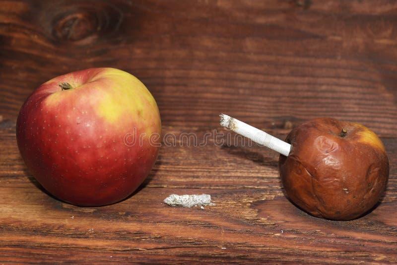 Deux pommes et une cigarette à l'arrière-plan en bois Mises à mort de fumée Aucun smok images stock
