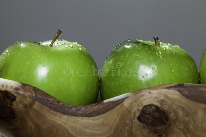 Deux pommes organiques frais lavées dans une cuvette en bois photos stock