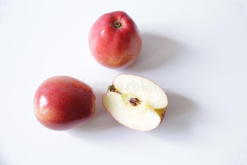 Deux pommes rouges et moitié d'une pomme d'isolement sur le fond blanc photo libre de droits