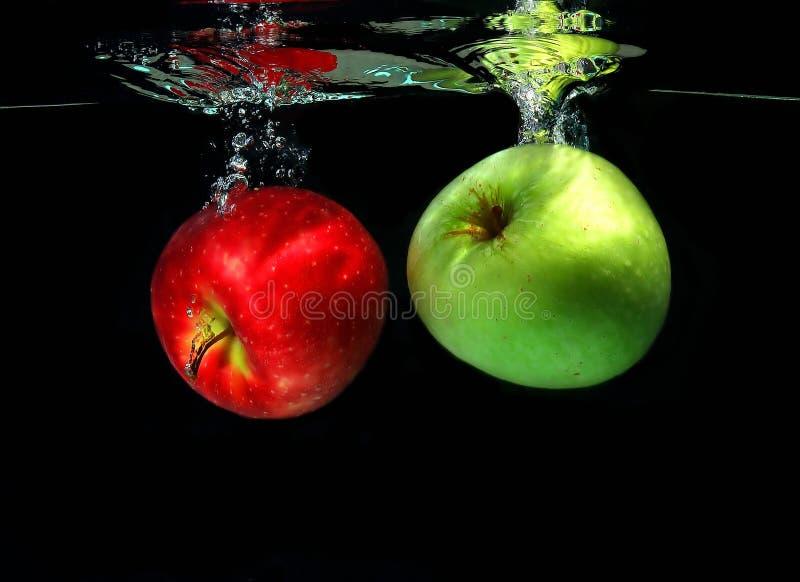 Deux pommes tombant dans l'eau photographie stock libre de droits