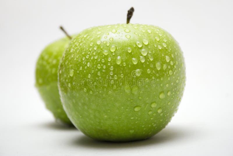 Deux pommes vertes avec des gouttes de pluie (vue de côté) photos libres de droits
