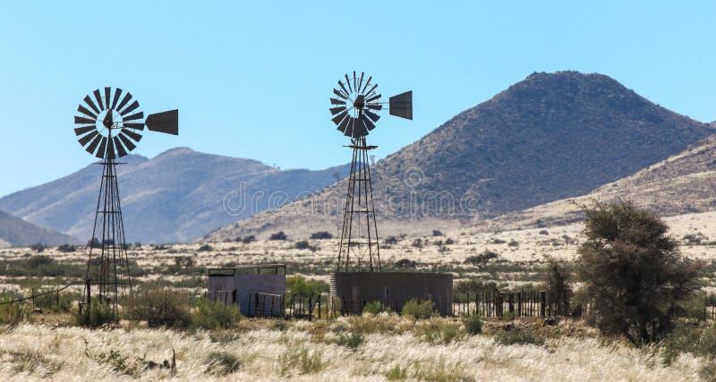 Deux pompes à eau de moulin à vent dans la chaleur harassent à la ferme image stock