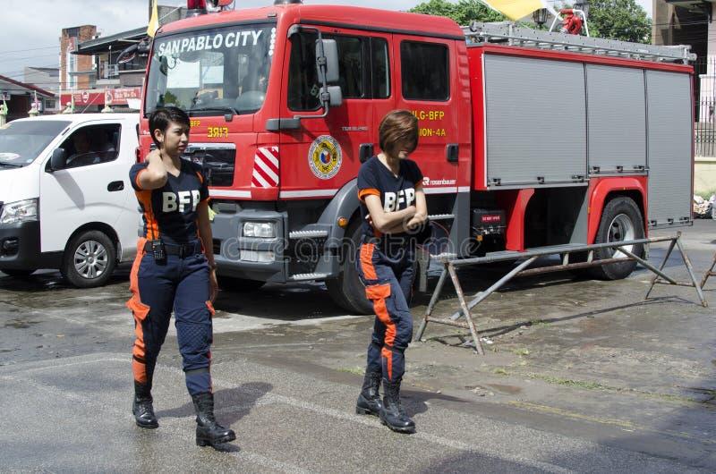 Deux pompiers en uniforme de dame marchant par camion de pompiers garé photographie stock libre de droits