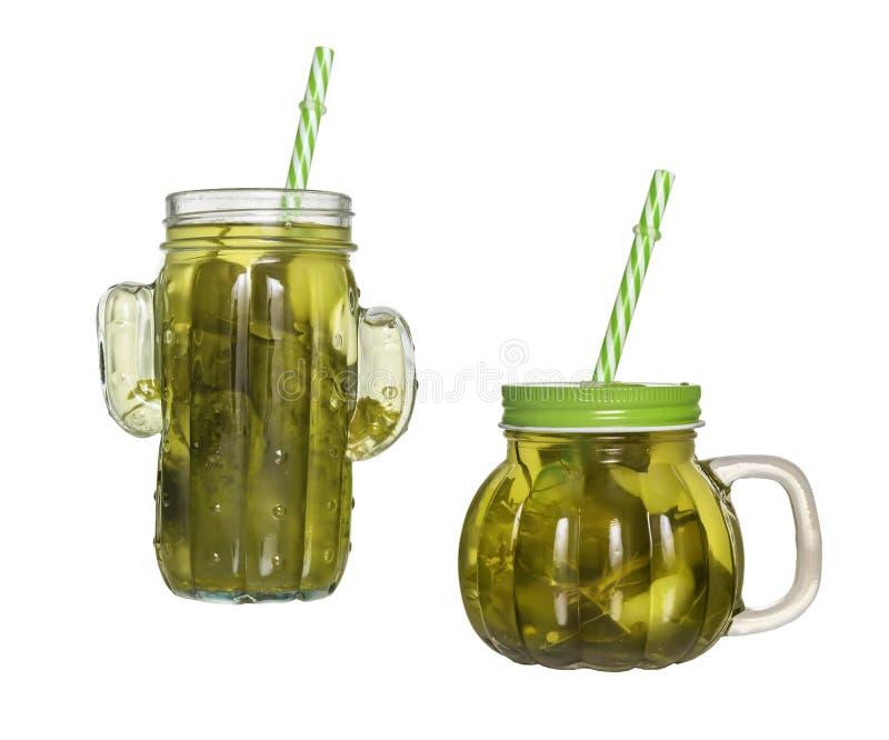 Deux pots en verre avec des couvercles et des tubes avec le concombre marinent d'isolement photographie stock libre de droits
