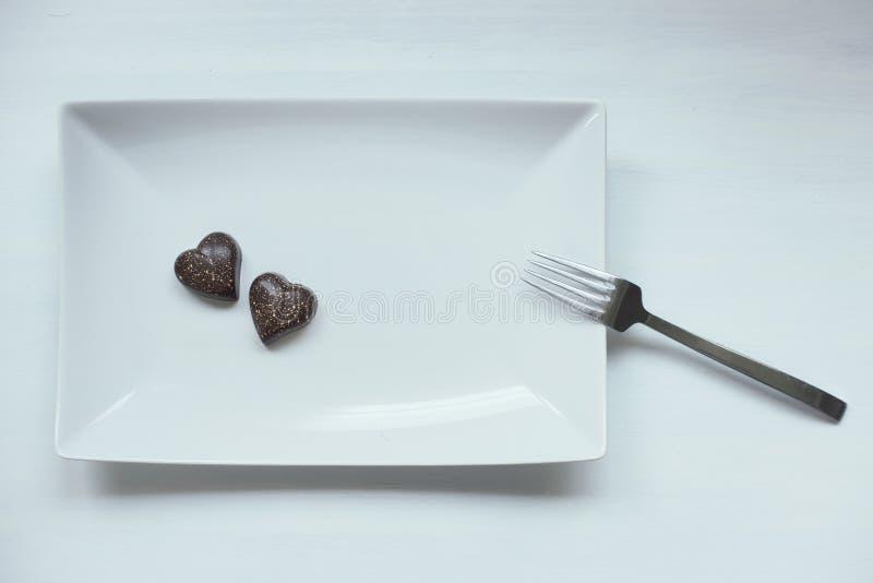 Deux pralines en forme de coeur de chocolat d'un plat blanc images libres de droits