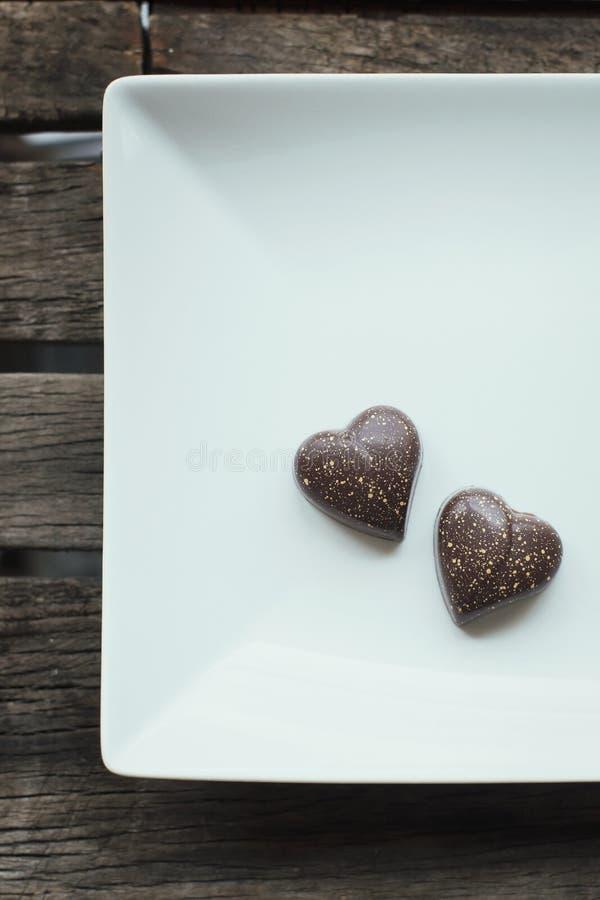 Deux pralines en forme de coeur de chocolat d'un plat blanc et en bois photographie stock libre de droits