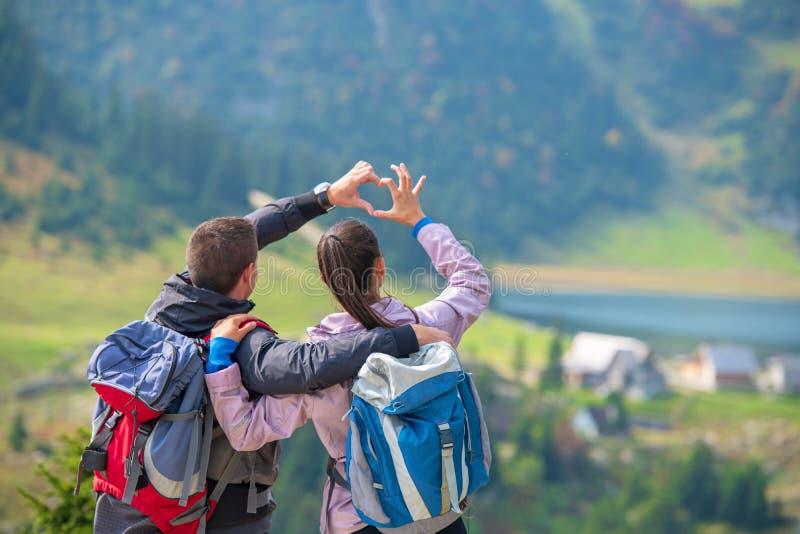 Deux randonneurs au point de vue dans les montagnes appréciant la belle vue de la vallée avec un lac images stock
