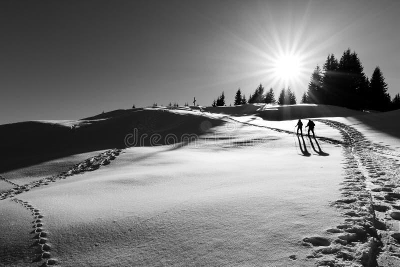 Deux randonneurs de ski marchant vers la croix de sommet images stock
