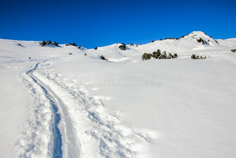 Deux randonneurs de ski marchant vers la croix de sommet Rayons de soleil et contre-jour photo stock