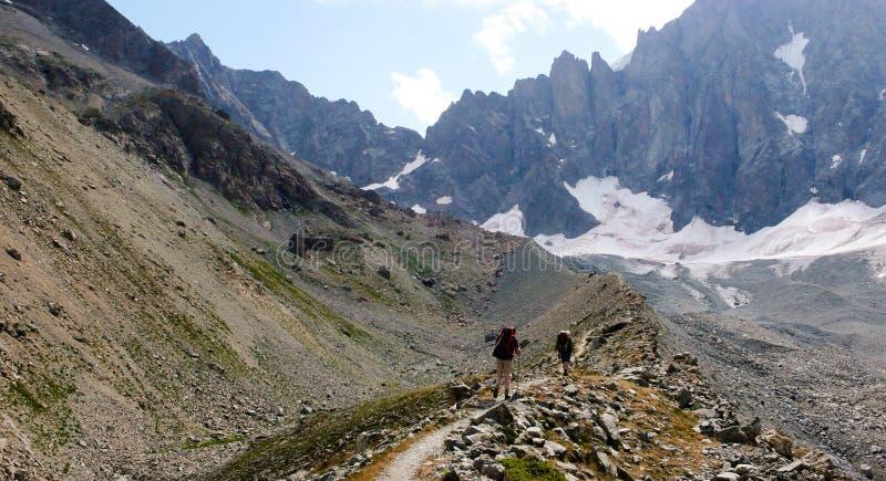 Deux randonneurs et grimpeurs de montagne trimardant le long d'une moraine de glacier photo stock