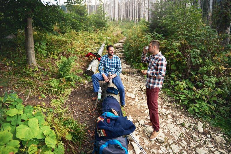 Deux randonneurs faisant une pause de trekking dans la forêt image libre de droits