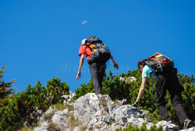 Deux randonneurs s'élevant vers la lune image stock