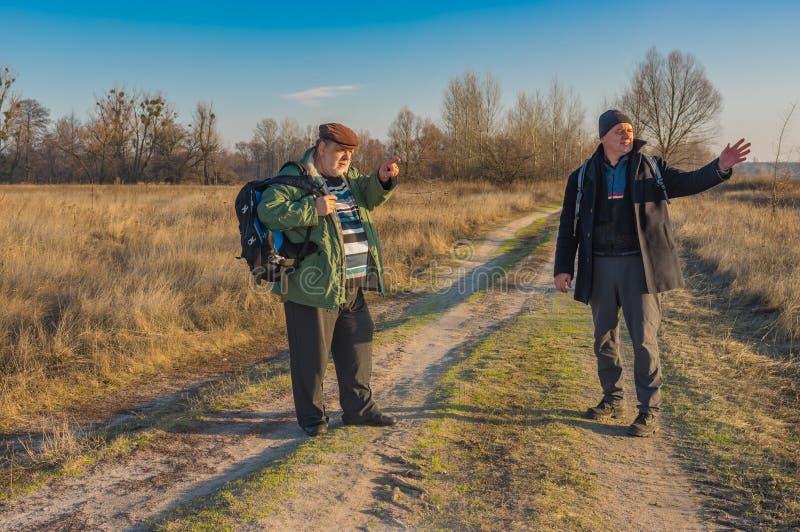 Deux randonneurs supérieurs avec des sacs à dos discutant le chemin correct tout en marchant sur une route de campagne image stock