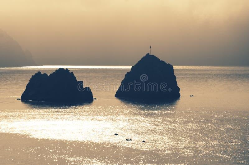 Deux roches et bateaux de pêcheur en mer au lever de soleil photo stock