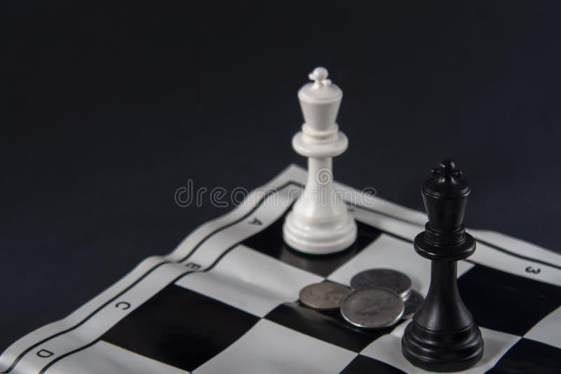 Deux rois d'échecs se tenant devant l'un l'autre, pièces de monnaie entre t images stock