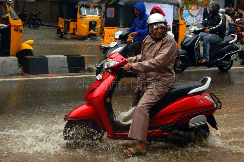 Deux-roues indien du lecteur d'homme supérieur sur une route inondée images libres de droits