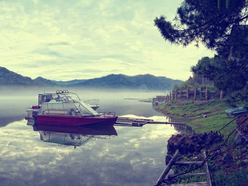Deux rouges et canots automobiles blancs amarrés au rivage d'un lac de montagne avec de l'eau calme dans un matin brumeux tôt photographie stock libre de droits