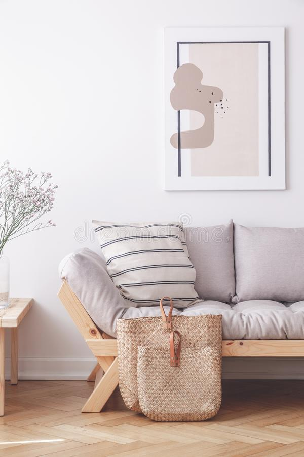 Deux sacs sur le plancher de l'appartement élégant avec le divan gris et la copie encadrée sur le mur photos libres de droits